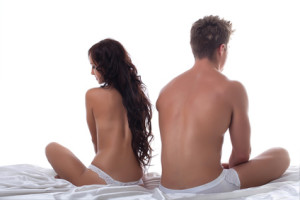 Concept of sexual disorders among partners. Upset young couple sitting apart in bed.